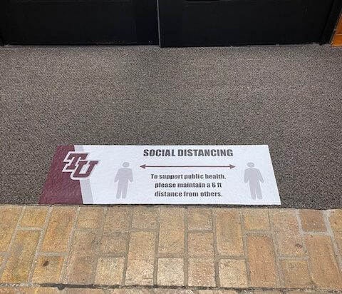 Social Distancing Sign shown on floor in the library
