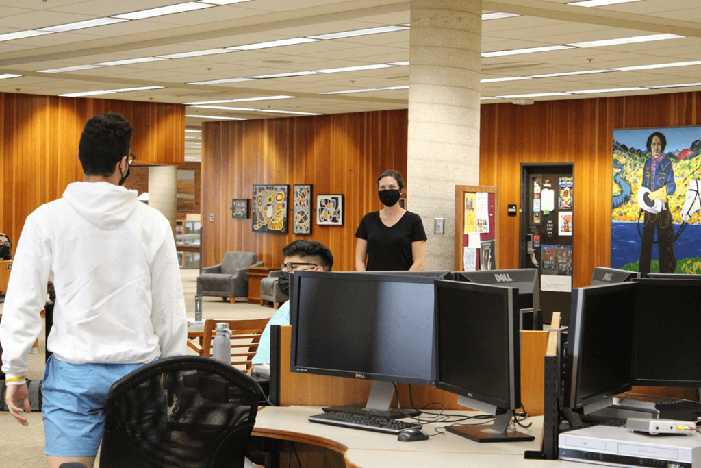 Librarian Anne Graf working with students in the Library Commons Area